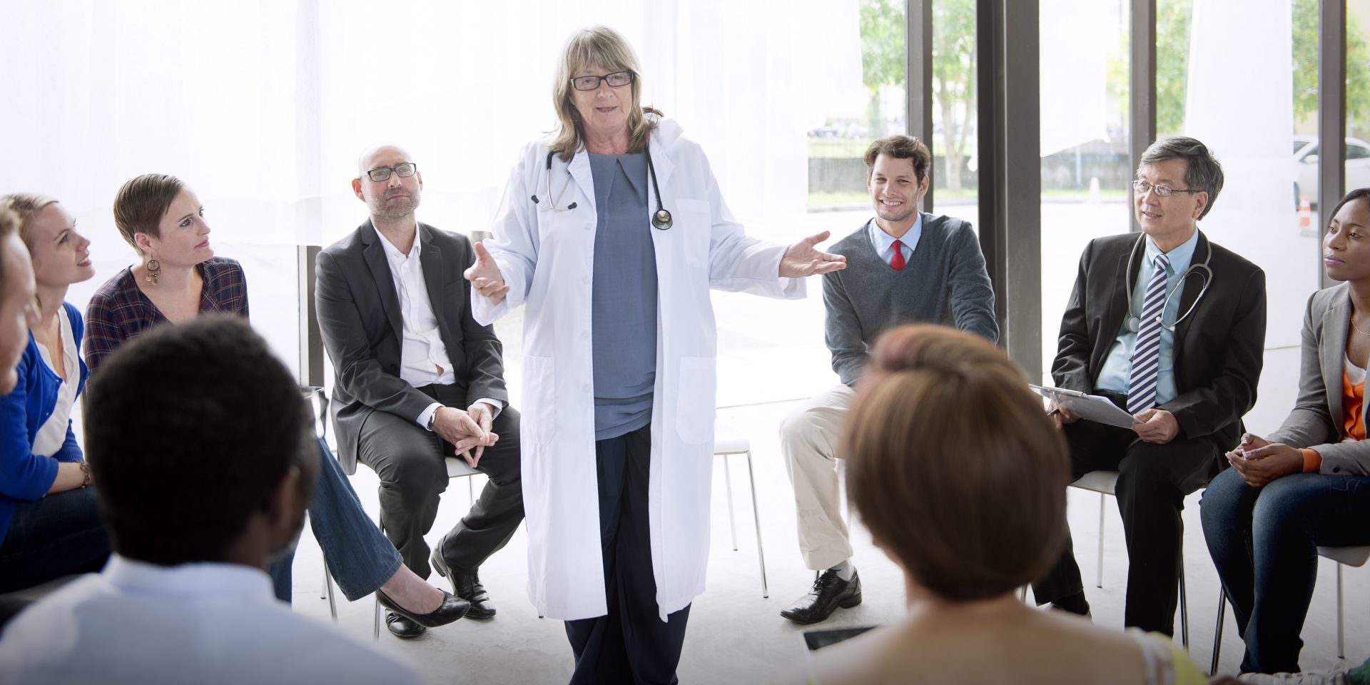 a medical physician in a white coat speaking to other doctors sitting around her
