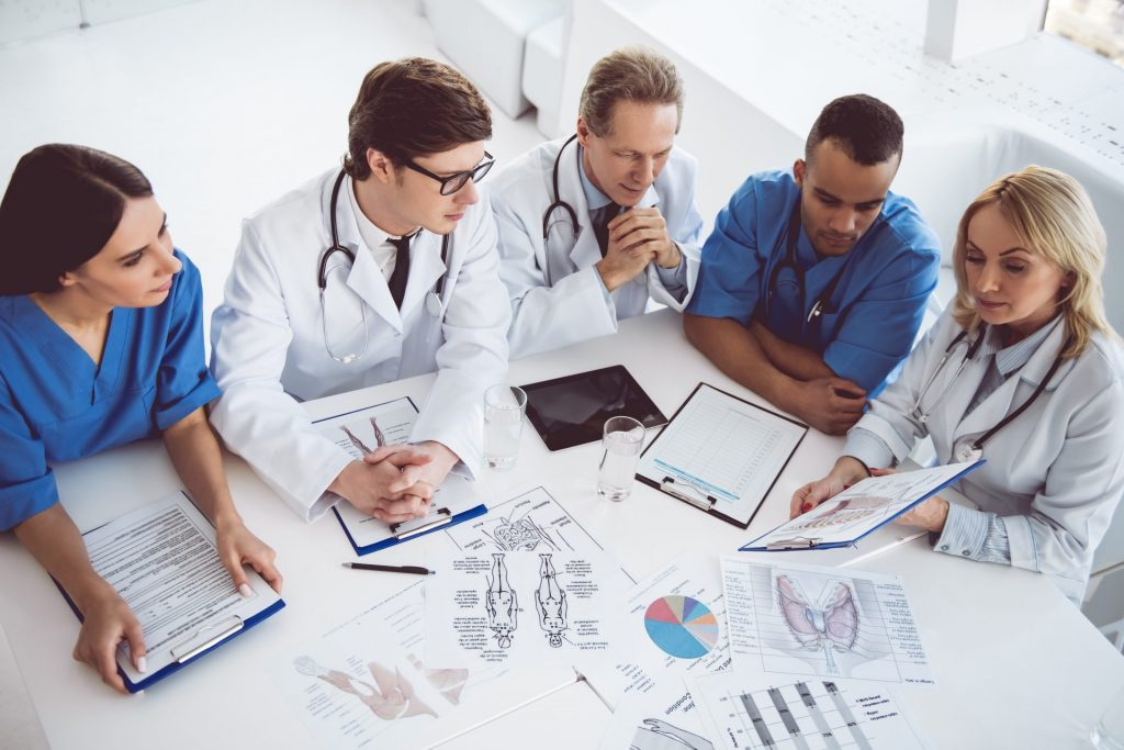 a group of doctors sitting at a table going over medical diagrams