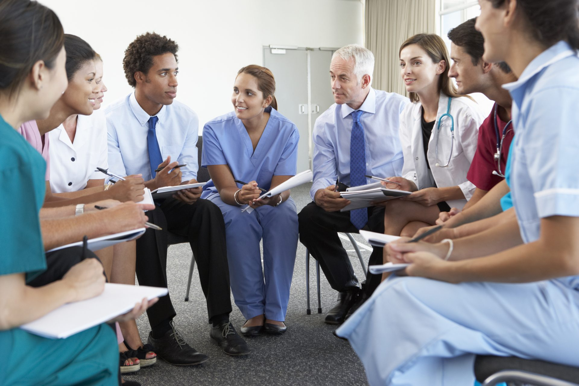 a group of doctors conversing in a circle of chairs